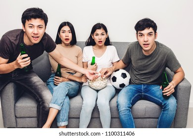 Group of friends eating popcorn and drinking beer together and watching soccer game on sofa at home.Friendship and party concept