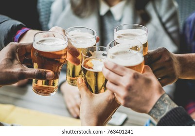 Group of friends enjoying a beer in brewery pub - Young people hands cheering at bar restaurant - Friendship and youth concept - Warm vintage filter - Main focus on bottom hand