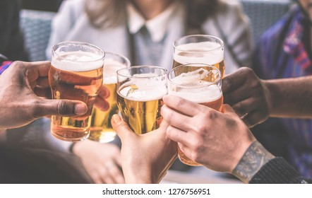 Group of friends enjoying a beer glasses in brewery english pub - Young people cheering at bar restaurant - Friendship and youth concept - Warm vintage filter - Main focus on left black hand