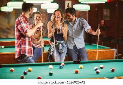 Group of friends enjoying in beer and playing billiard in bar
