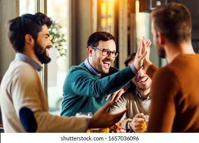 Group of friends enjoying in beer pub