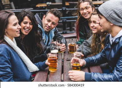 Group of friends enjoying a beer at pub in London, toasting and laughing. Four girls and two boys in their twenties having fun together. Friendship and lifestyle concepts