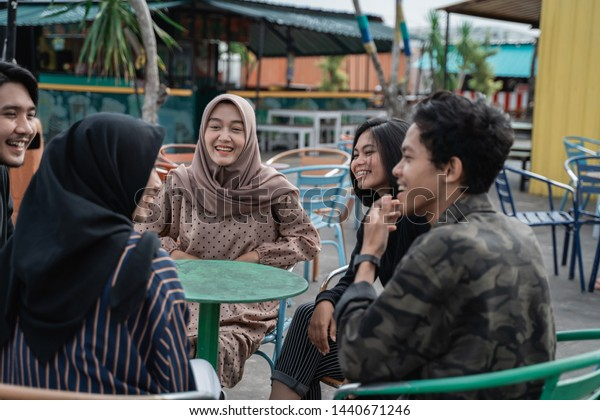 Group of friends enjoying chatting and sharing knowledge at the cafe rooftop