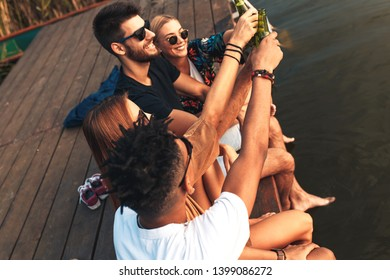 Group of friends enjoying a day at the lake. They sitting on pier talking, laughing and drinking beers.