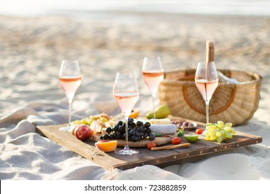 Group of friends enjoying an evening meal with wine at a Beach