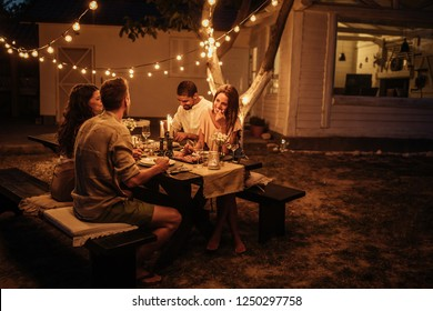Group of friends enjoying food and drinks together outside
