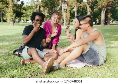 A group of friends enjoying ice cream together in a park on a sunny day.
