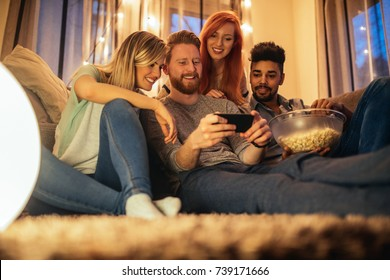 A group of friends enjoying a late night movie on the couch with snacks.