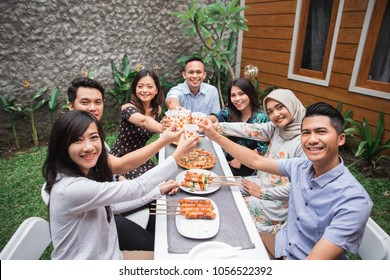 Group of friends enjoying meal in the backyard and cheers with their glass