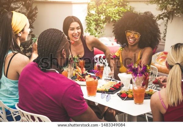 Group of friends enjoying meal and having fun outdoors - People talking and laughing togheter at the restaurant