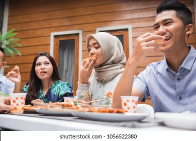 Group of friends enjoying meal at outdoor party in backyard