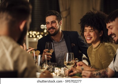 Group of friends are enjoying a meal in a restaurant. They are are talking and laughing while eating and drinking wine. - Shutterstock ID 595702277