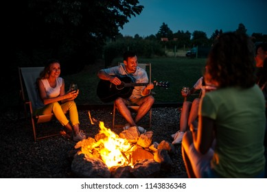 Group of friends enjoying music around the firepit at night.