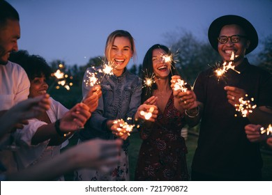 Group of friends enjoying out with sparklers. Young men and women enjoying with fireworks.
