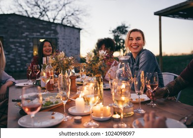 Group of friends enjoying outdoor party in garden restaurant . Millennials enjoying dinner outdoors