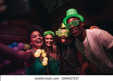 Group of friends enjoying at party in the bar and taking selfie with smart phone. Cheerful en and women partying and celebrating St.Patrick's Day at night club.