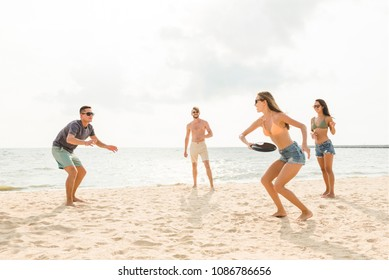 Group of friends enjoying summertime, playing at the beach on holidays
