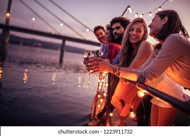 Group of friends enjoying sunset at the party by the river