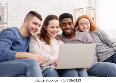Group of friends enjoying time together and looking at laptop, watching videos at home