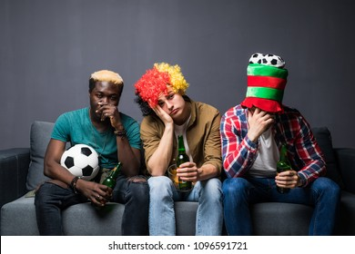 group of friends fanatic football fans watching soccer game on television with beer bottles and pizza suffering stress and crazy nervous on couch sad and dejected as if their team is loosing.