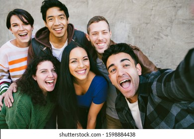 Group of friends gather together to capture a selfie with happy expressions