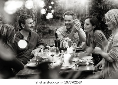 Group of friends gathered around a table in a garden on a summer evening to share a meal and have a good time together.Black and white