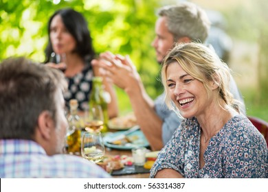 Group of friends gathered around a table on a terrace in the summer to share a meal, focus on a blond  woman. Shot with flare