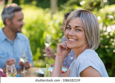 A group of friends gathered to share a meal around a table in the garden. Focus on a beautiful woman looking at the camera