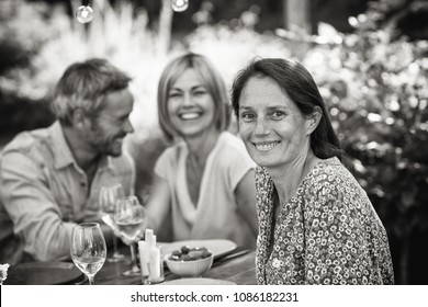 A group of friends gathered to share a meal around a table in the garden. Focus on a beautiful woman looking at the camera. Black and white