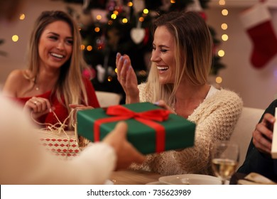 Group of friends giving Christmas presents at home