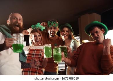Groupe d'amis avec des lunettes de bière verte au pub. Fête de la Saint-Patrick