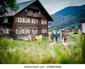 group of friends going for a hike in nature and walking through a village by passing a wooden old house