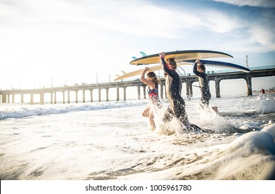Group of friends going to surf at the beach
