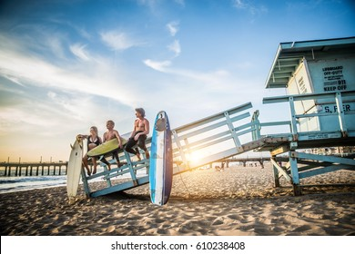 Group of friends going to surf at the beach - Young adults bonding at the beach