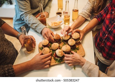 Group of friends grabbing some burgers and beer.
