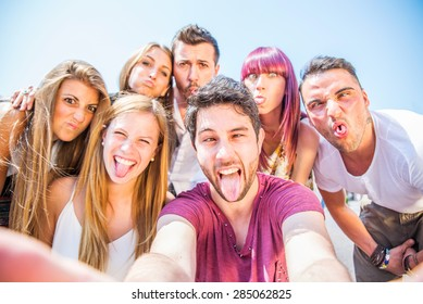 Group of friends grimacing in front of the camera - Young happy people having fun at party and making funny faces while photographing themselves
