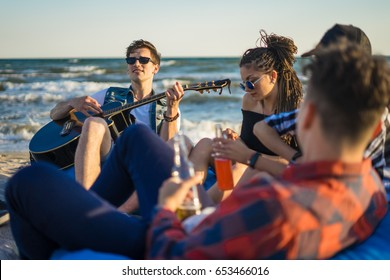 group of friends with guitar and alcohol on the beach party - Young hipster people on summer vacation playing guitar near the sea and drinking alcohol. Happy youth time. they sit on bean bags
