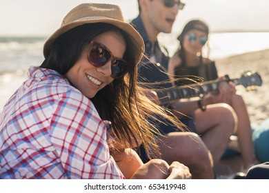 group of friends with guitar on the beach party on sunset- Young hipster people on summer vacation playing guitar near the sea. girl in hat is smiling and looking at camera
