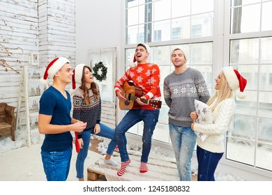 A group of friends with  guitar and singing at home on Christmas