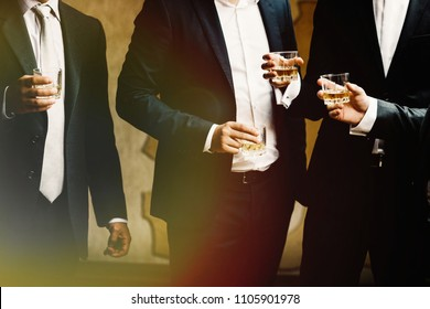 Group of friends guys with glasses of whiskey