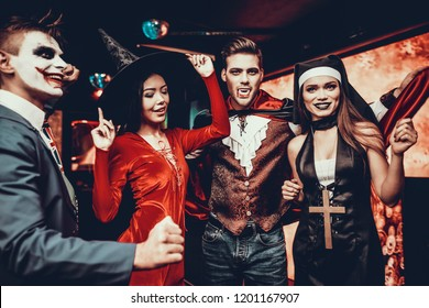 Group of Friends in Halloween Costumes Dancing. Young Smiling People Wearing Costumes having Fun and Dancing Together at Halloween Party in Nightclub. Celebration of Halloween