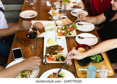 Group of friends hands with fork having fun eating variety food on the table