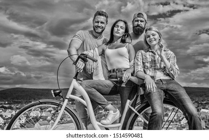 Group friends hang out with bicycle. Company stylish young people spend leisure outdoors sky background. Bicycle as best friend. Youth likes cruiser bike. Cycling modernity and national culture.