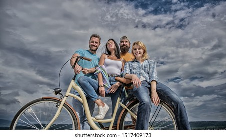 Group friends hang out with bicycle. Youth likes cruiser bike. Cycling modernity and national culture. Company stylish young people spend leisure outdoors sky background. Bicycle as best friend.