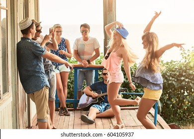 Group of friends hanging out on vacation at an old wooden cabin porch by the sea while two girls are dancing and a guy is taking pictures with his smartphone