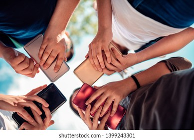 Group of friends hanging out and using smart phones on a sunny day