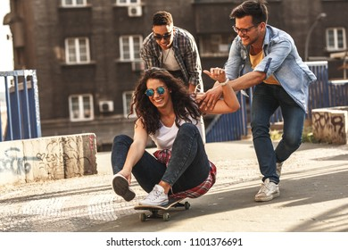 Group of friends hangout at the city street.Female sitting on skate board while friends pushing her from behind.