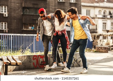 Group of friends hangout at the city street.Female standing on skate board while friends teach her to ride.
