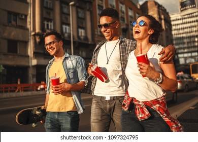 Group of friends hangout at the street.They embrace each other and walks around at the city downtown.Drinking cold juice.