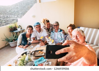 group of friends have fun together celebrating and dining at home in the outdoor terrace with smile and laugh - man take a slefie picture with phone - friendship and family concept mixed ages people